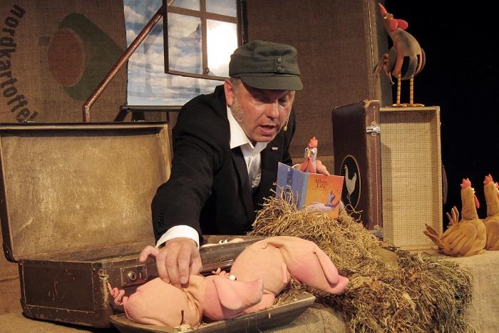 Theaterspieler mit Huhn und Schweinen