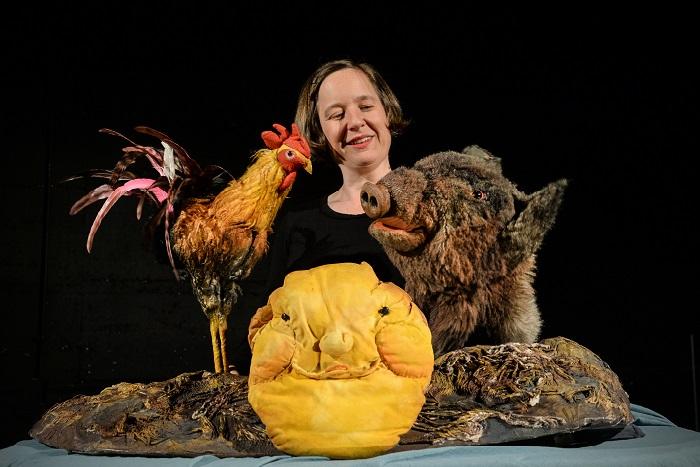Abbildung einer Theaterspielerin mit einem Hahn, Schwein und Pfannkuchen